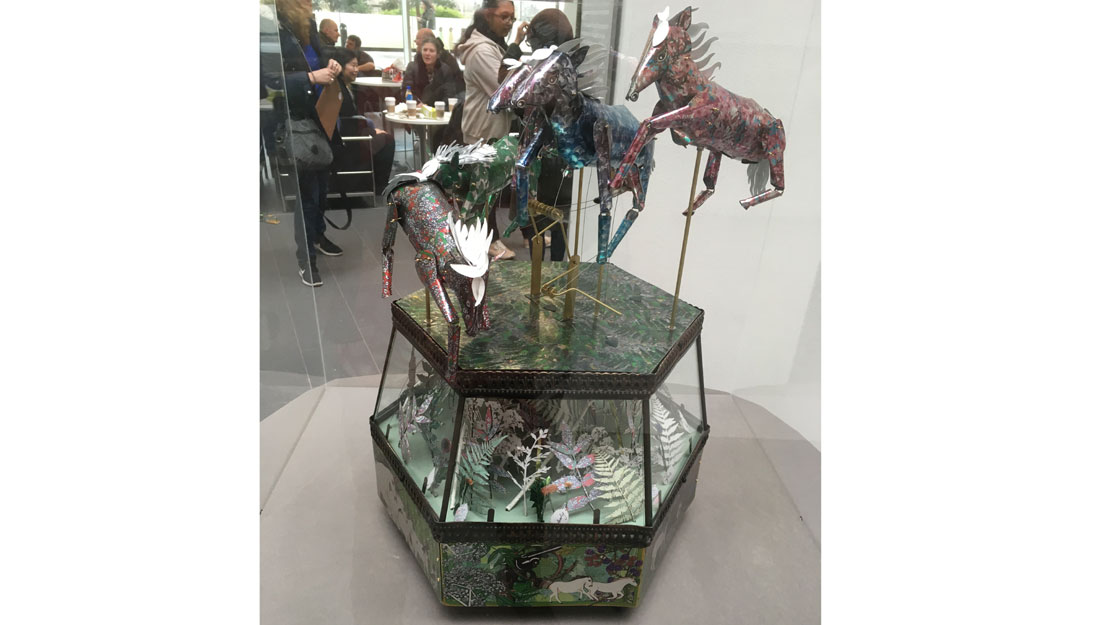 metal horses over a hexagon filled with metal leafs and bushes