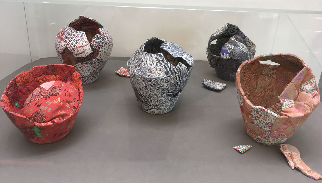 colourfully patterned vases made of fabric, which are broken at the top of the rim