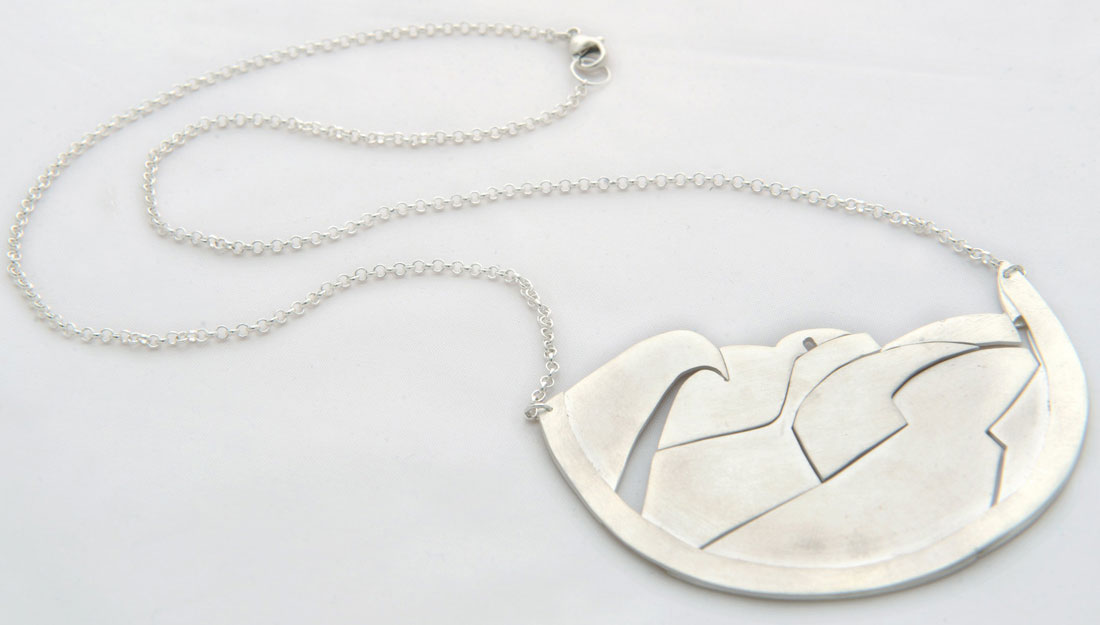 silver necklace with a pendant consisting of several small parts