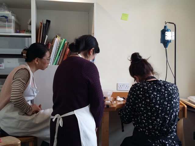 Two women are watching a woman who Shelanu member drills a hole in the pendant