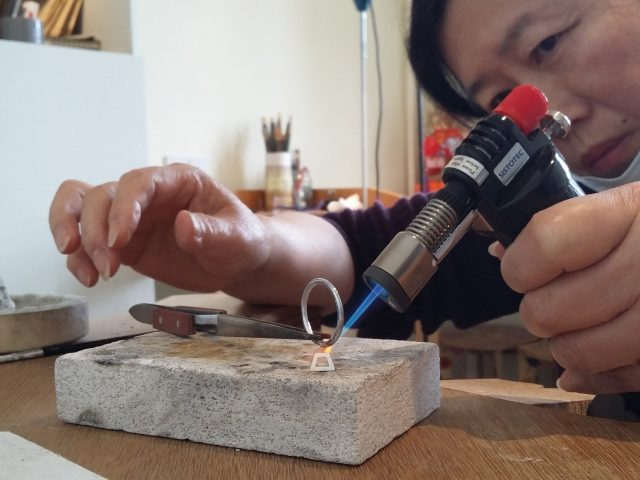 Woman uses the gas for the fusion of the ring and the rectangular