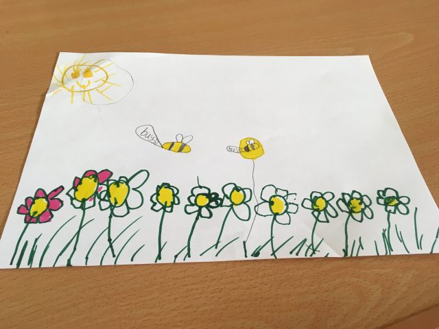 a meadow with flowers painted by a child