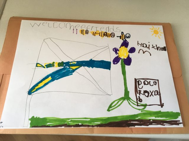 A child painted a flag with flowers and bees.
