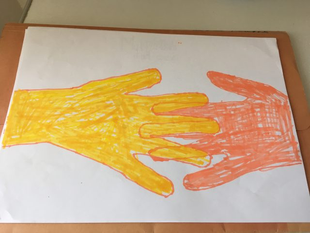 A child painted two hands clinging to each other.