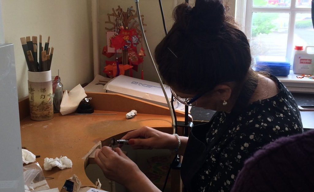 Shelanu member drills a hole in the pendant for a necklace