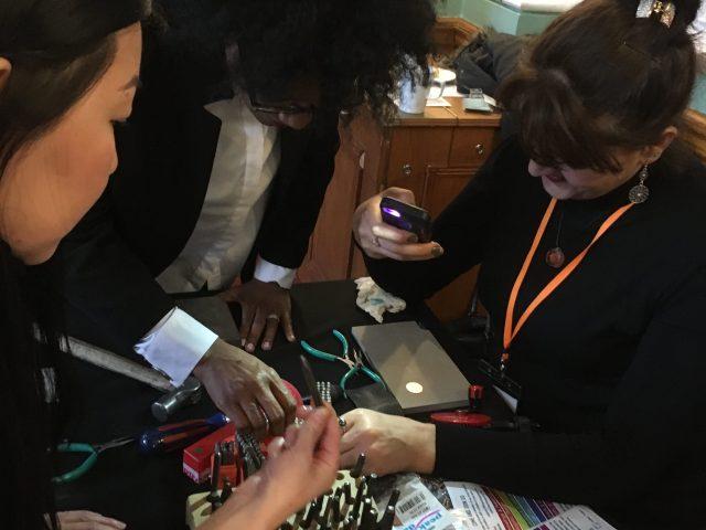making a stamp metal key ring with volunteers