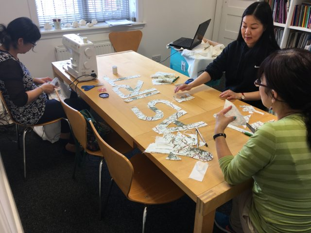 Shelanu members cutting out the mapped letters