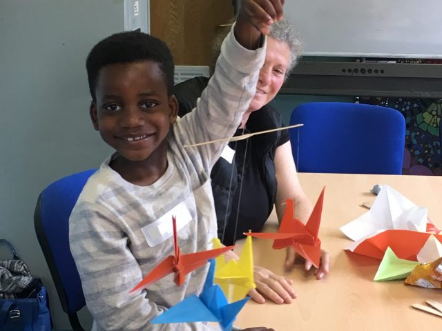 Child from ASIRT group proudly showing their finished origami crane