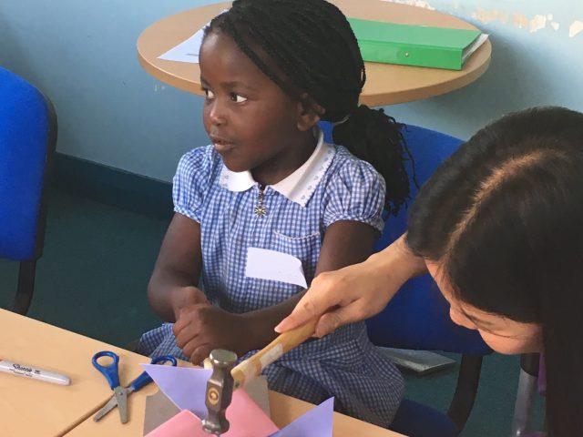 Shelanu member helping child to finish paper windmill