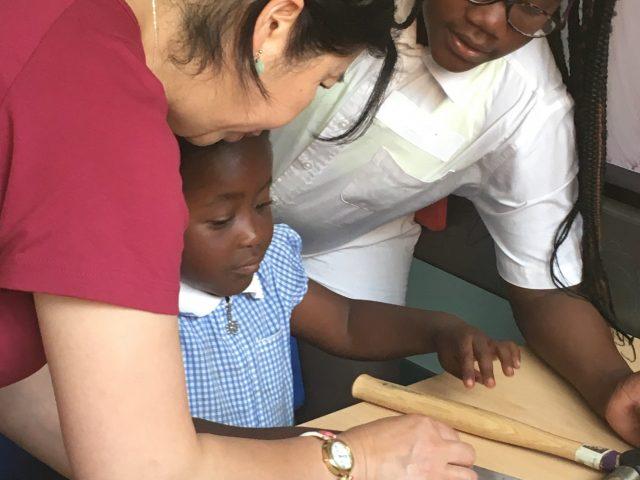 Shelanu member showing children how to stamp metal