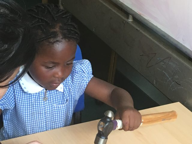 Child using a hammer to stamp letters on metal