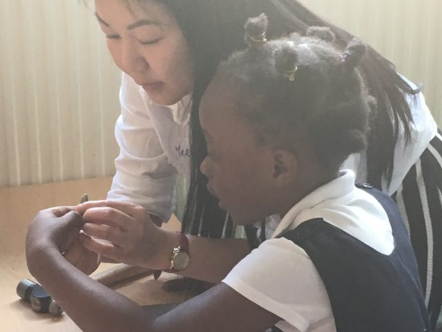Shelanu member helping child pick out metal stamps