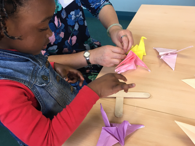 Shelanu member helping child from ASIRT group to make origami crane mobile