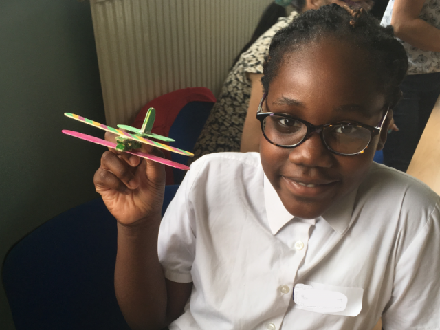 Child from ASIRT group holding up their finished wooden toy aeroplane