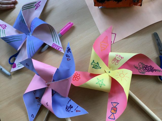 Finished paper windmills with childrens drawings on them.