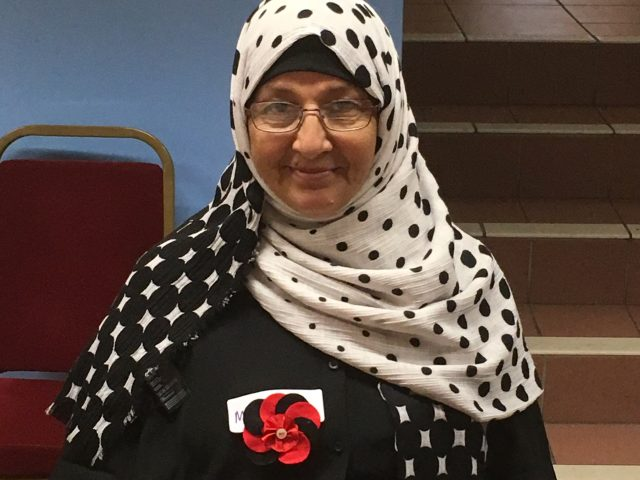 Refugee Action client proudly wearing their finished fabric badge