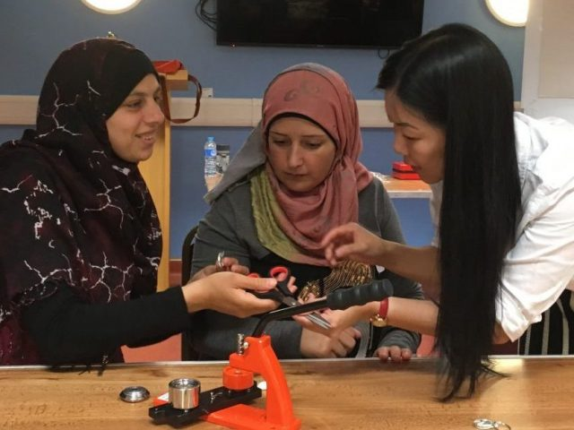 Shelanu member showing Refugee Action client's how to make fabric badges using badge machine