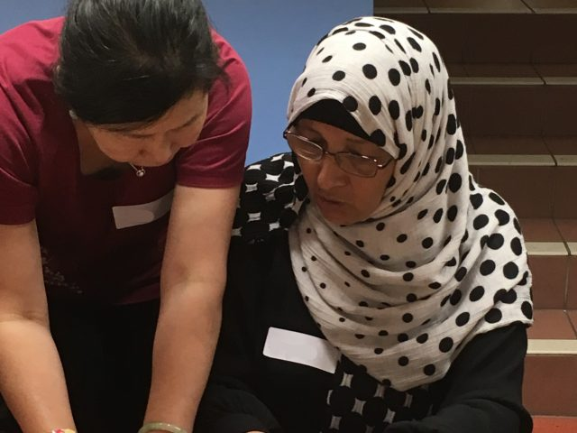 Shelanu member helping Refugee Action client measure out material for fabric keyring