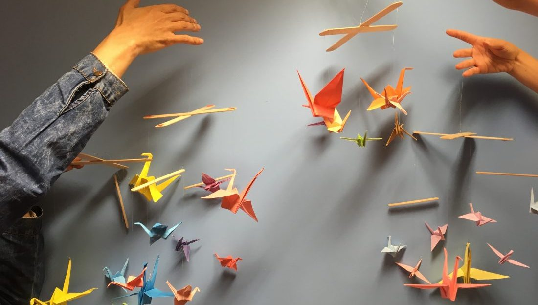 Hands holding up four finished colourful origami paper crane mobiles.