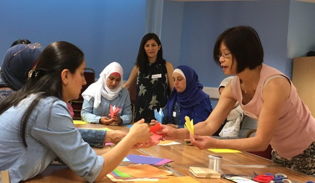 Shelanu member teaching Refugee Action clients how to fold origami cranes