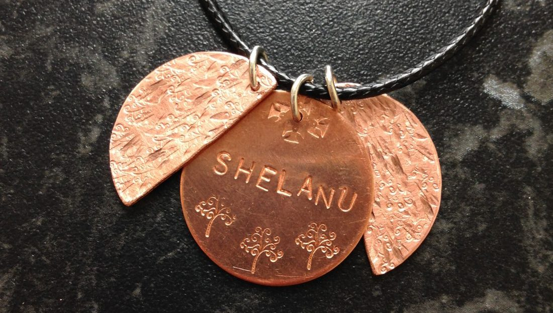 A necklace on whose copper disc a woman stamped the name Shelanu.
