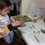 A lady and her son learn how to make a bead together