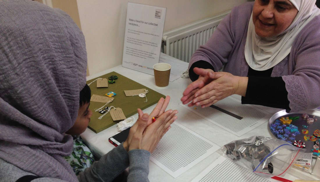 A partipant from the Women's Maker Movement shows a woman and her child how to make a bead